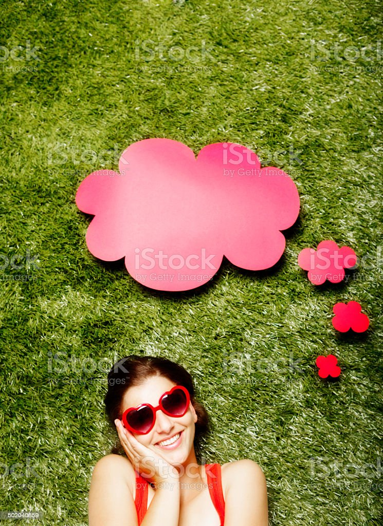 Pretty woman in heart-shaped sunglasses with speech bubble smiles flirtatiously royalty-free stock photo