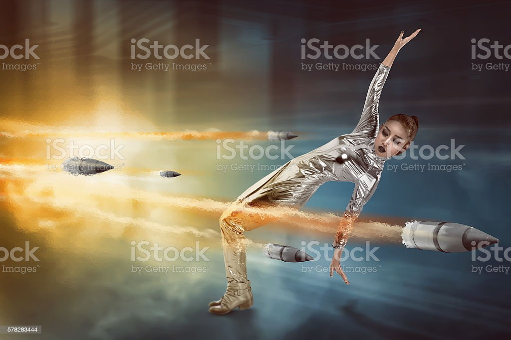 Pretty woman in latex costume dodging bullet stock photo