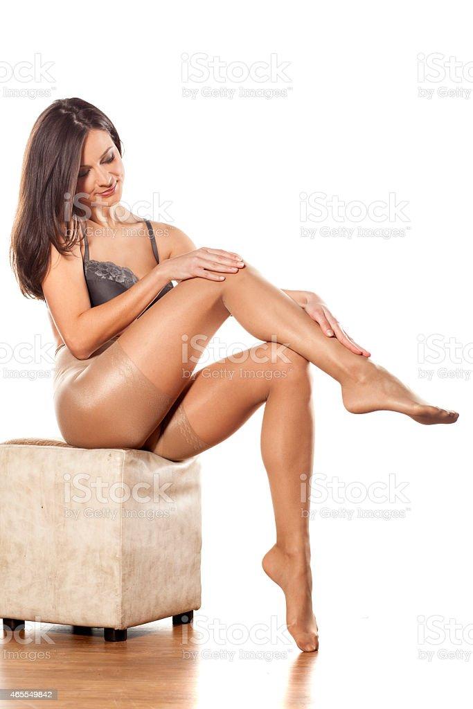 Pretty woman in nylon stockings and bra posing on white stock photo