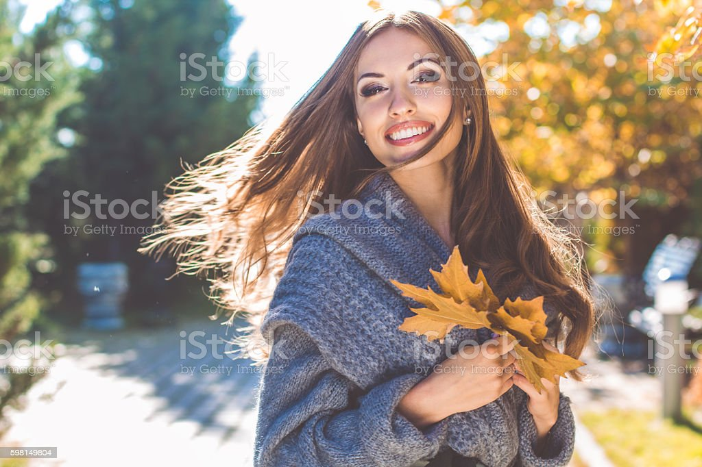 Pretty woman in park with autumn yellow leaves stock photo