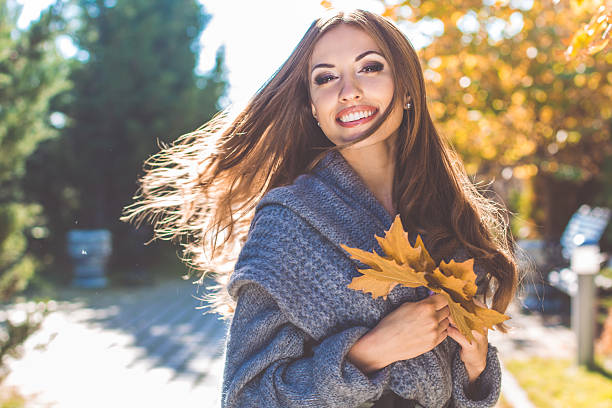 pretty woman in park with autumn yellow leaves - waldmode stock-fotos und bilder