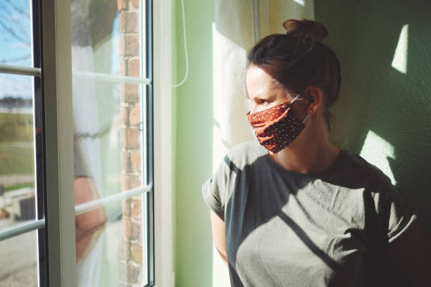 Pretty woman in quarantine with mask, looks out the window stock photo
