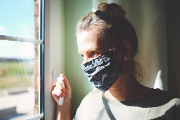 Hübsche Frau in Quarantäne mit Maske, schaut aus dem Fenster – Foto