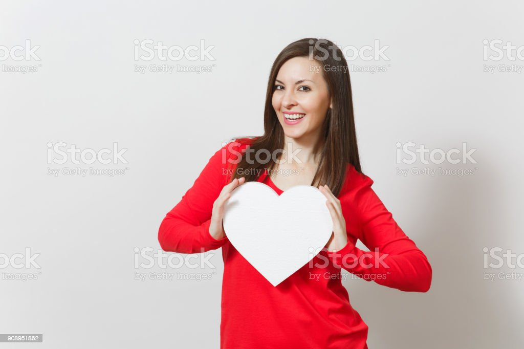 Pretty woman in red clothes holding big white heart in hands isolated on white background. Copy space for advertisement. With place for text. St. Valentine's Day or International Women's Day concept. stock photo