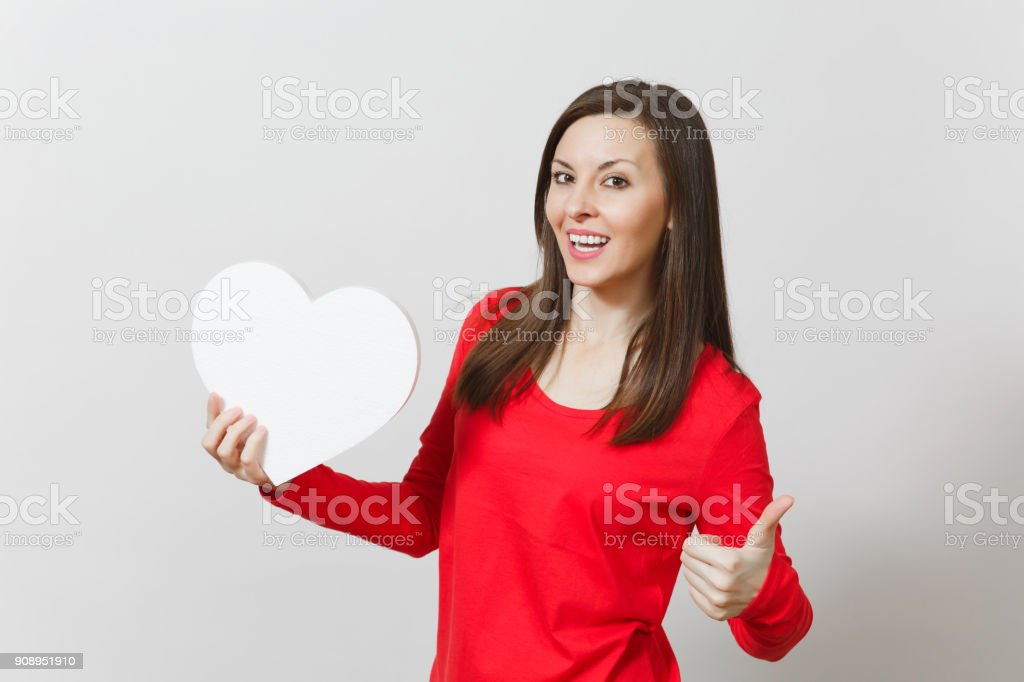 Pretty woman in red clothes showing thumb up, holding big white heart in hands isolated on white background. Copy space for advertisement. St. Valentine's Day or International Women's Day concept. stock photo