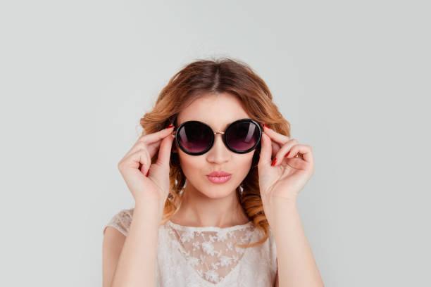 hübsche frau in runde sonnenbrille lächelnd über hellen grauen hintergrund - haarschnitt rundes gesicht stock-fotos und bilder