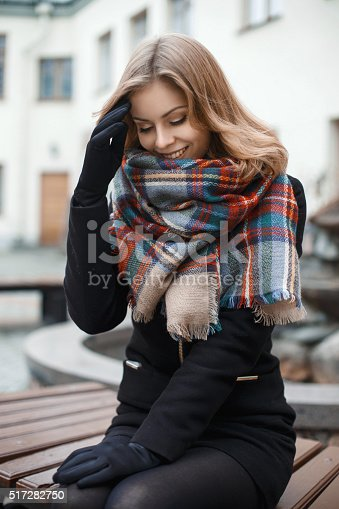 1051172208 istock photo Pretty woman in stylish clothes sitting on a bench 517282750