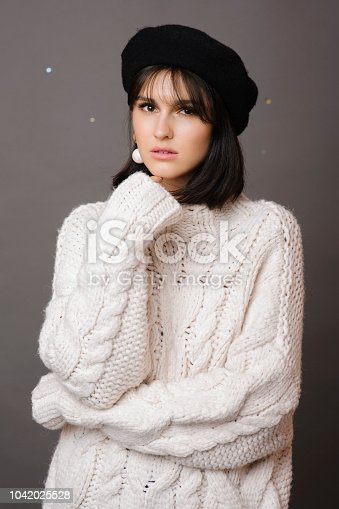 Attractive woman in white knitted sweater looking at camera on gray background
