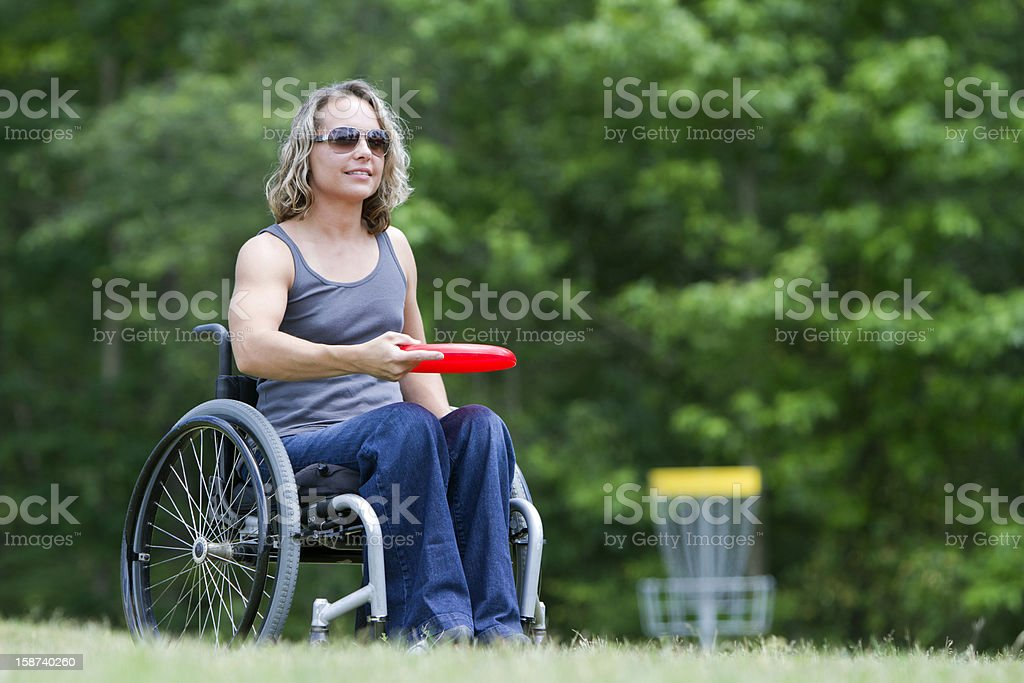 Pretty Woman in Wheelchair Playing Frisbee royalty-free stock photo