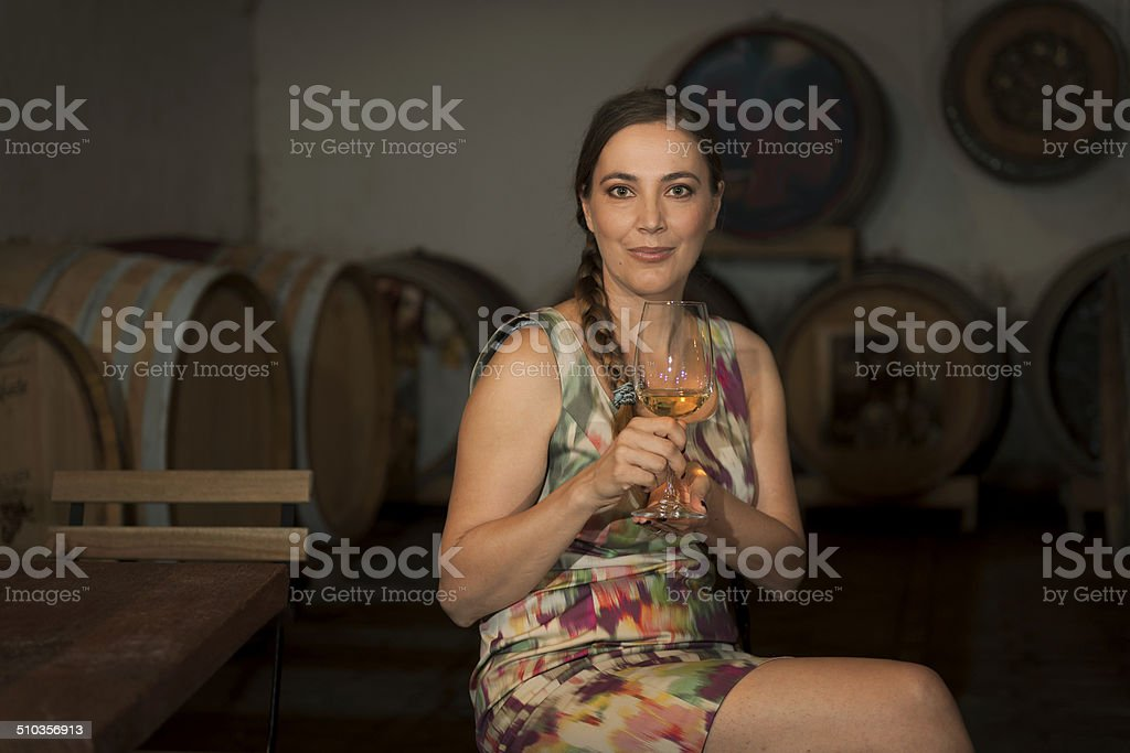 Pretty Woman in Winery Cellar with Glass of White Wine stock photo