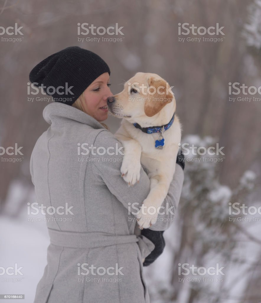 Pretty woman in winter clothes is nose to nose with adorable healthy puppy stock photo