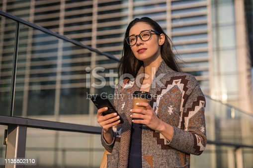 istock Pretty woman is drinking coffee and using smart phone 1135802110