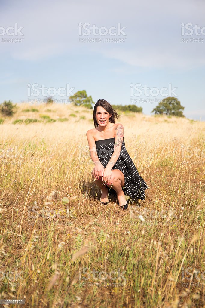 Pretty woman is squatting in countryside and looks into camera stock photo