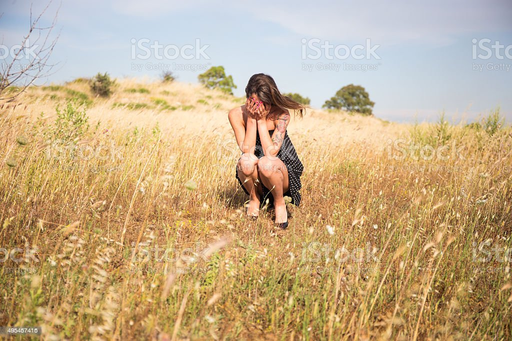 Pretty woman is squatting in countryside and smiles stock photo