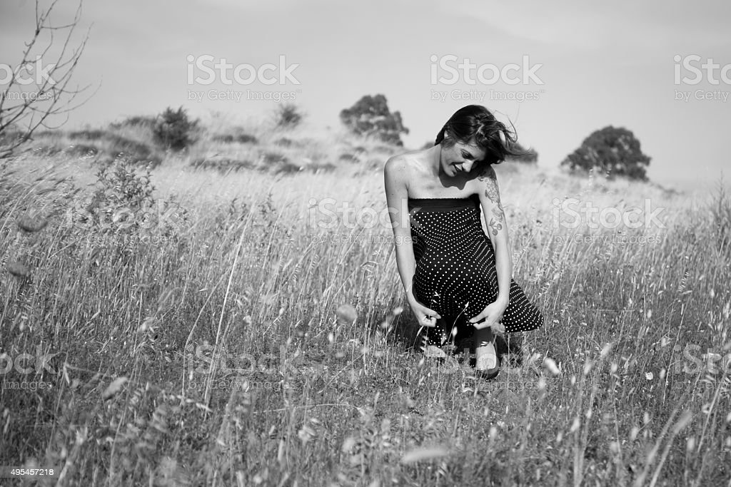 Pretty woman is squatting in countryside. Black and white stock photo