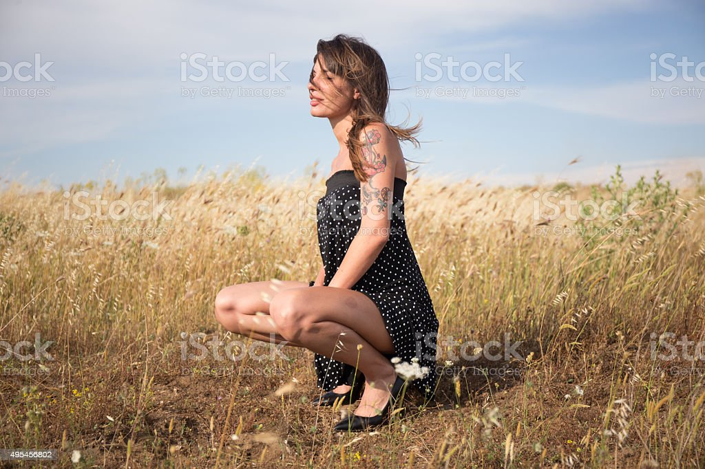 Pretty woman is squatting in countryside stock photo