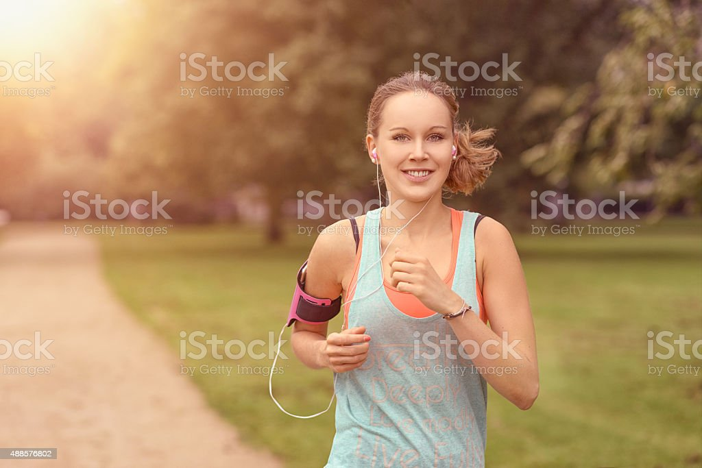 Pretty Woman Jogging at the Park with Headphones Half Body Shot of a Pretty Athletic Woman Jogging at the Park with Headphones and Smiling at the Camera, with copy space 2015 Stock Photo