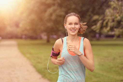 Pretty Woman Jogging At The Park With Headphones Stock Photo - Download Image Now