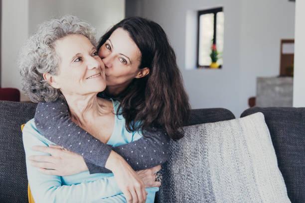 Hübsche Frau küsst ältere Mutter und umarmt sie von hinten – Foto