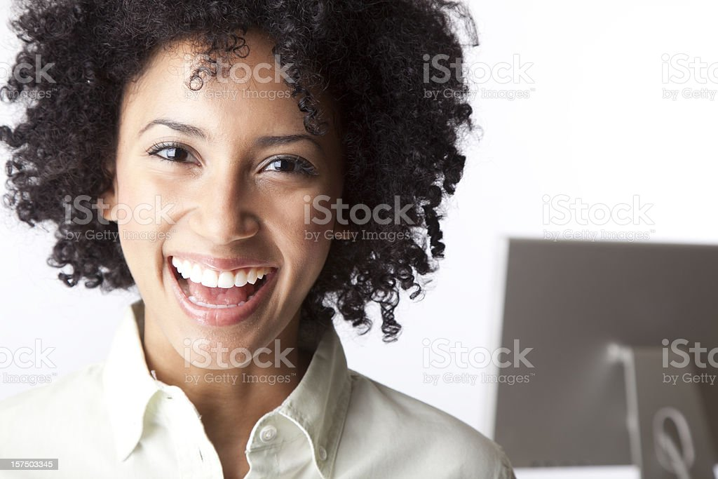 pretty woman laughing with computer in background royalty-free stock photo