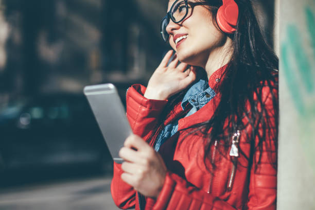 Pretty woman listening music with earphones from a phone stock photo