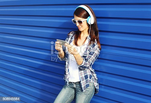 istock Pretty woman listens to music in headphones and using smartphone 508545584