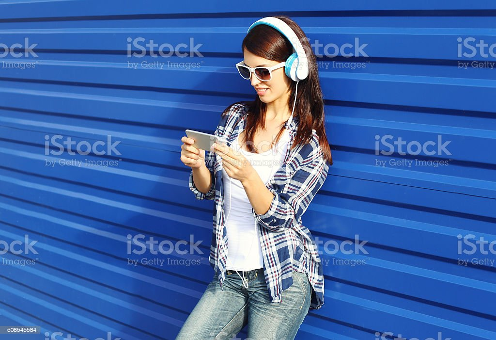 Pretty woman listens to music in headphones and using smartphone stock photo