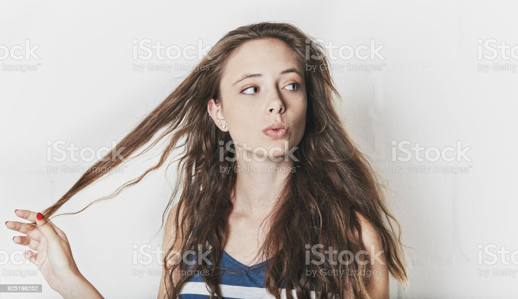 Pretty woman looks sideways, playing with her hair stock photo