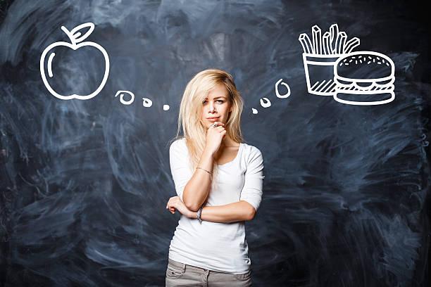hübsche frau macht eine wahl zwischen schlechte essen - gesundheitsfragen stock-fotos und bilder