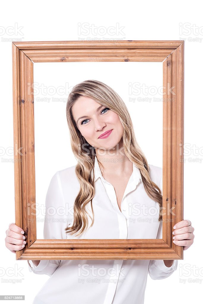 Pretty  woman posing behind  wooden frame stock photo