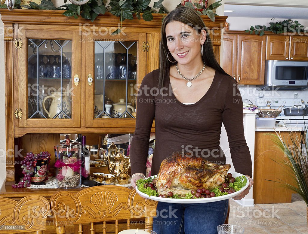 Pretty Woman Presenting Turkey for Thanksgiving or Christmas royalty-free stock photo