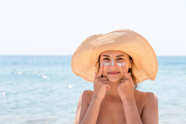 Pretty woman protects her skin on face with sunblock at the beach Pretty woman protects her skin on face with sunblock at the beach. suntan lotion stock pictures, royalty-free photos & images