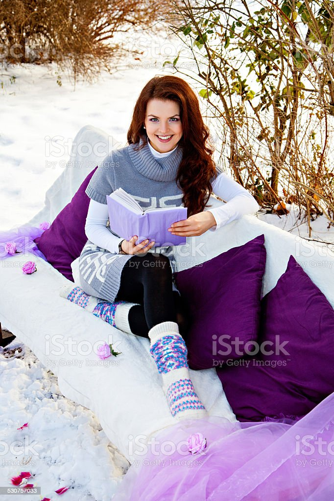 Pretty woman reading a book outdoors stock photo