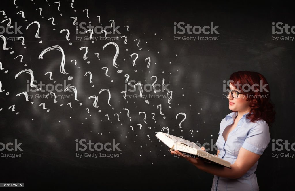 Pretty woman reading a book with question marks coming out from it stock photo