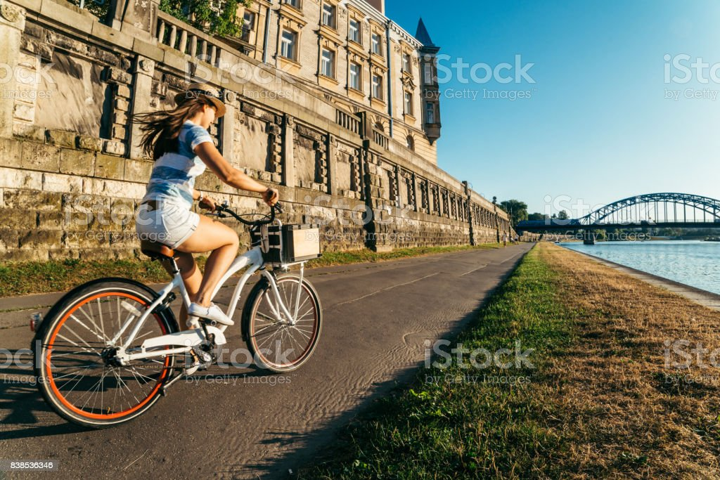 pretty woman ride bicycle on embankment of Wisla river stock photo