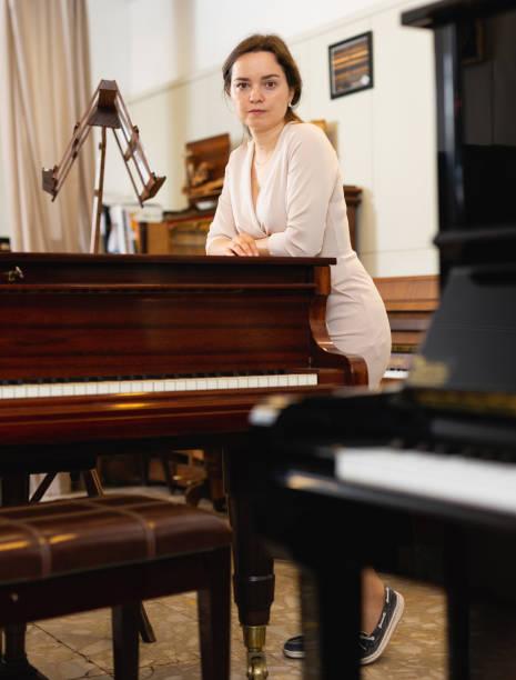 hübsche frau verkäufer in klavier-musik-shop - klavier verkaufen stock-fotos und bilder