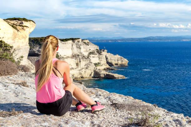 jolie femme assise à falaises à bonifacio - randonnée corse photos et images de collection
