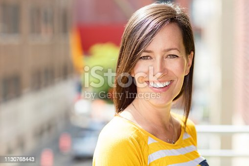 Pretty Woman Smiling at the camera. She is beautiful on a blur background