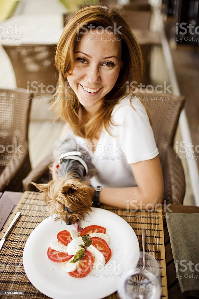 Pretty woman smiling to camera while her yorky eating salad royalty-free stock photo