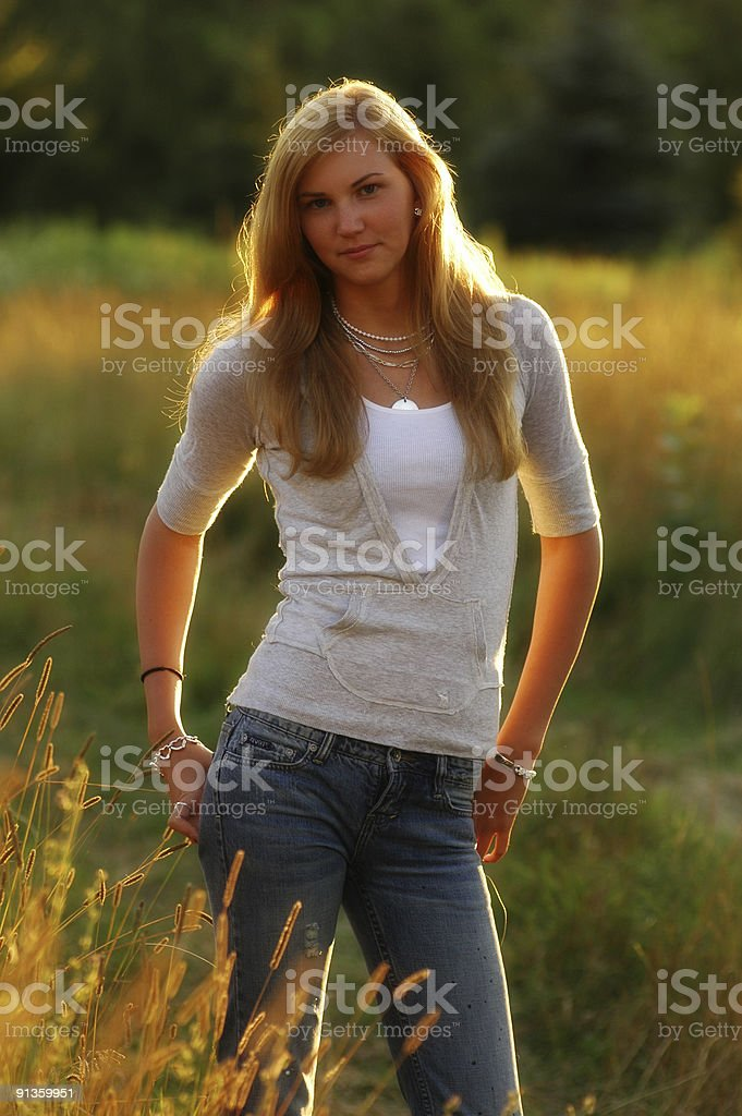 Pretty woman standing in field at sunset royalty-free stock photo