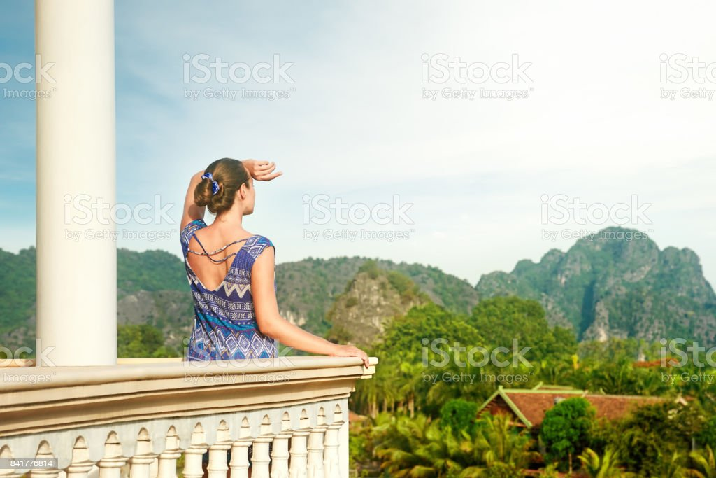 Pretty woman standing on the balcony watching beautiful mountains view stock photo