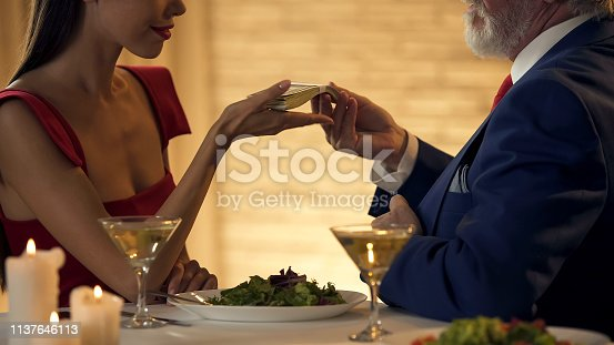 488389267istockphoto Pretty woman taking money from old partner, mistress exchanging love for money 1137646113