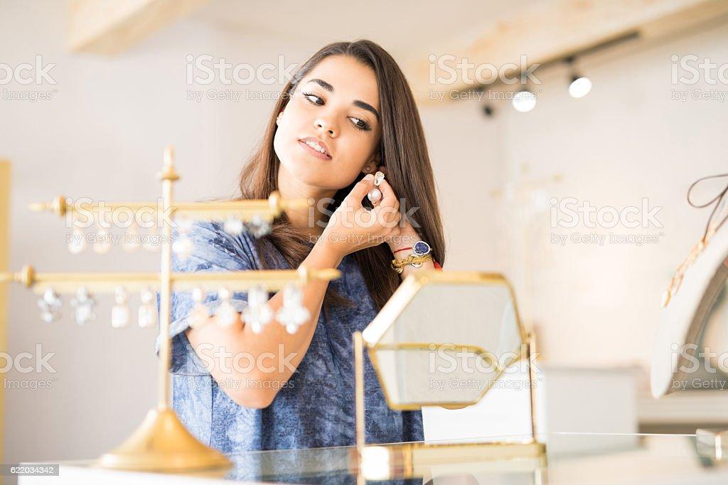 Pretty woman trying on some earrings - foto de acervo