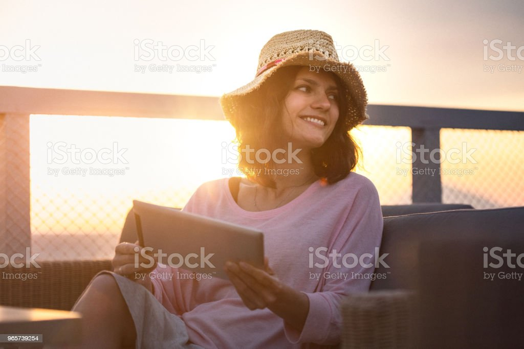 Pretty woman using digital tablet on vacation at sunset - Royalty-free Adult Stock Photo