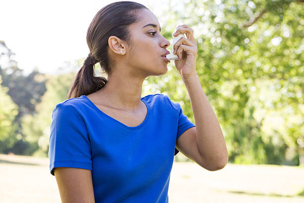 Pretty woman using her inhaler stock photo