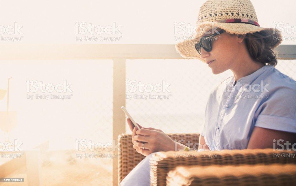 Mooie vrouw met behulp van slimme telefoon op vakantie bij zonsondergang - Royalty-free Alleen volwassenen Stockfoto