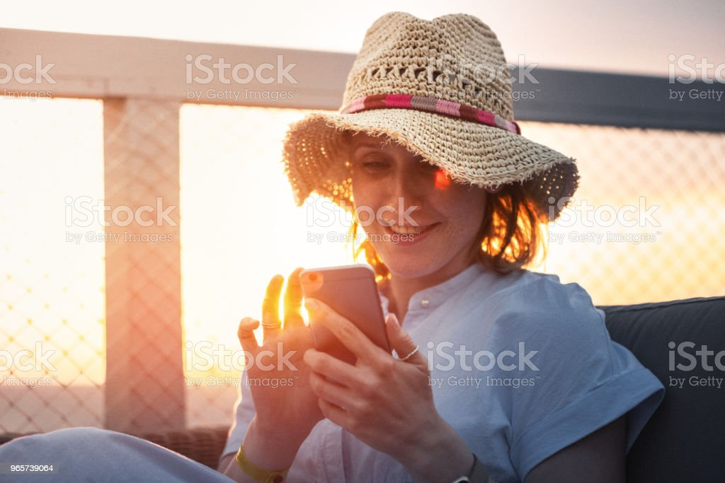 Pretty woman using smart phone on vacation at sunset - Royalty-free Adult Stock Photo