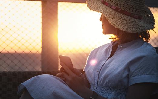 Mooie Vrouw Met Behulp Van Slimme Telefoon Op Vakantie Bij Zonsondergang Stockfoto en meer beelden van Alleen volwassenen