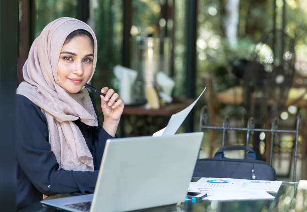 pretty woman wearing hijab in front of laptop search and doing office work, business, finance and workstation concept. - pakistan foto e immagini stock