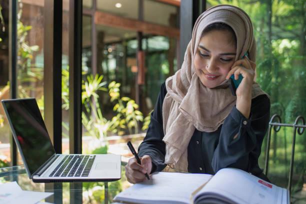 Mujer bonita llevar hijab frente a la búsqueda de portátil y haciendo trabajo de oficina, negocios, finanzas y estación de trabajo concepto. - foto de stock